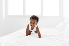 Smiling Toddler Crawling On Bed