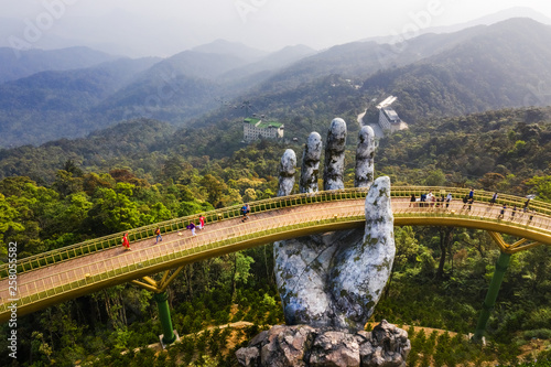 Top aerial view of the famous Golden Bridge is lifted by two giant hands in the tourist resort on Ba Na Hill in Danang, Vietnam Canvas Print