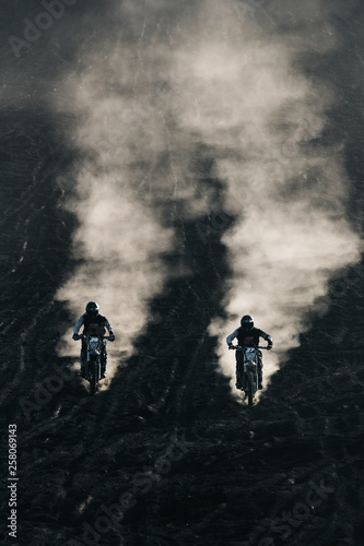 Fotografía Two friends racing on custom retro style cafe racer black motorcycles on the bla
