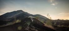 Three Friends Racing On Dirt Enduro Motorcycles On The Black Lava At Sunrise On Mount Batur, Bali, Indonesia
