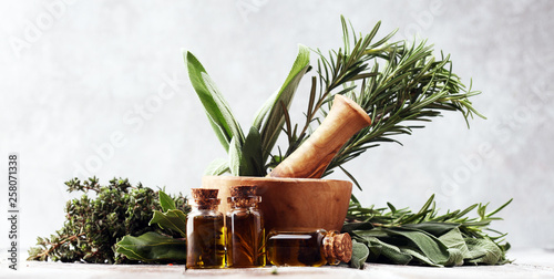 Fototapeta Fresh herbs from the garden and the different types of oils for massage and aromatherapy on table obraz