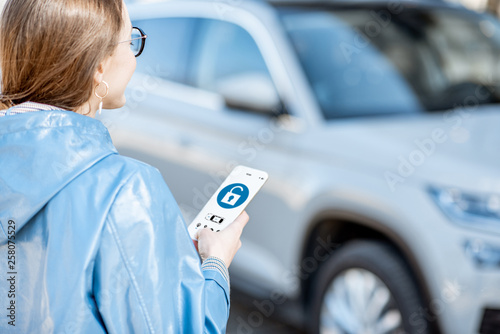 Woman unlocking car using mobile application on a smart