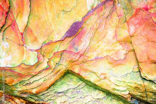 Multicolored rock wall from bottom sediments red orange dark rays crack smooth Obraz na płótnie