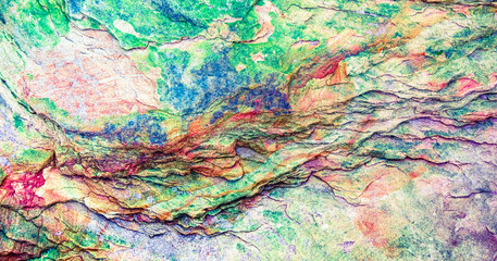 FototapetaMulticolored rock wall from bottom sediments red orange dark rays crack smooth