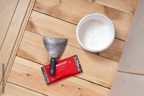 Fotografía A putty bucket, trowel and emery grater are on the floor