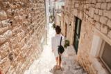 Fototapeta Uliczki - Young girl walking through ancient narrow streets on a beautiful summer day