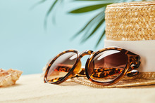 Selective Focus Of Sunglasses And Straw Hat Near Seashell In Summertime Isolated On Blue