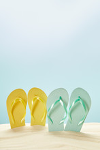 Summer Yellow And Blue Flip Flops In Golden Sand Isolated On Blue