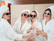 Spa leisure time. BFF relaxation. Sunglasses, bathrobes and towel turbans on. Females clinking champagne. Cheers.