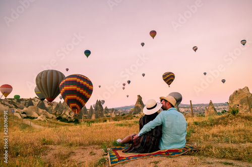 Poster Rose clair / pale happy young couple during sunrise watching the hot air balloons of Kapadokya Cappadocia Turkey