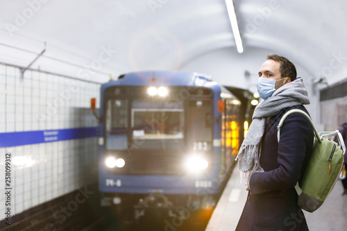 Fototapeta Ill young man wrapped in scarf feeling sick, wearing protective mask against transmissible infectious diseases and as protection against the flu in public, waiting for the train at subway station. obraz