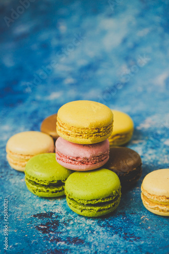 Aluminium Prints Macarons Variety of colorful macarons over a blue background