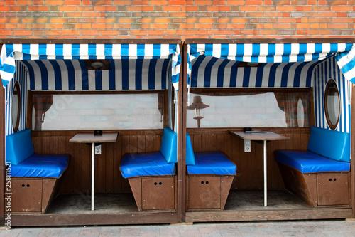 Fotobehang Muziekwinkel Überdachte Sitzbänke mit blau-weisser Markise