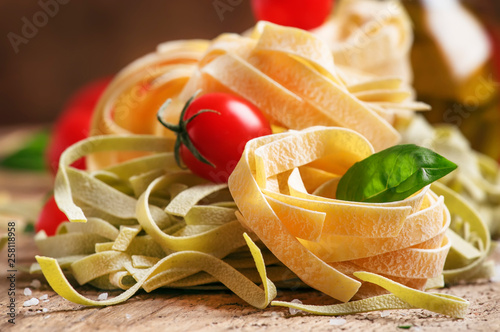 Concept of italian food cooking with green and yellow tagliatelle pasta, red che Obraz na płótnie