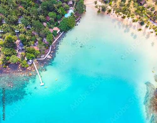 Poster Turquoise Aerial view of tropical beach at island hotel resort with blue sea water and coconut palm trees, beautiful summer vacation holidays destination, drone top-down panorama