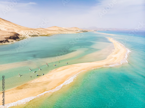 Canvas Prints Canary Islands Aerial view of beach in Fuerteventura island with windsurfers learning windsurfing in blue turquoise water during summer vacation holidays, Canary islands from drone