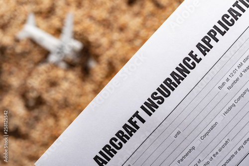 Photo aircraft insurance application wtih a blurred crashed aircraft model on back