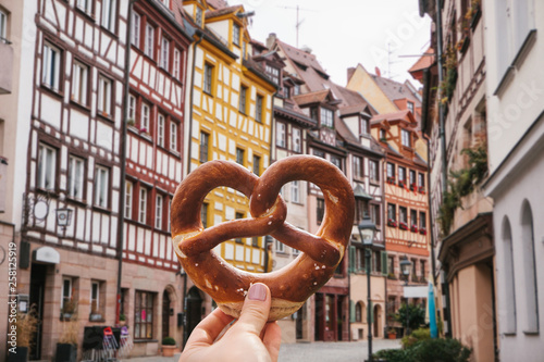 Fotografía  A girl holds in her hand a traditional German pretzel on the background of a beautiful architecture or street in Nuremberg in Germany