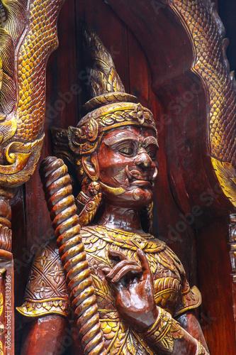 Fotografia  old wooden statue in a buddhistic temple