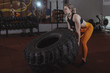 Young female crossfit athlete with strong toned body lifting heavy wheel, exercising at the gym. Attractive sportswoman working out at crossfit box gym, copy space