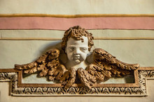 Closeup Of An Architectural Detail. Bas-relief Of A Cherub With Wings, Enriched With Stucco Friezes, Decorations, Flowers And Frames. Ancient Sculpture Attached To A Plastered And Painted Wall.