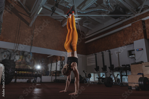 Full length shot of a sportswoman doing handstand at crossfit box gym Canvas Print