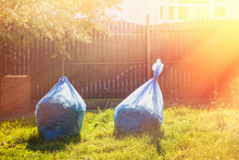 Two Bags Of Compost On The Grass In The Sun At Sunset