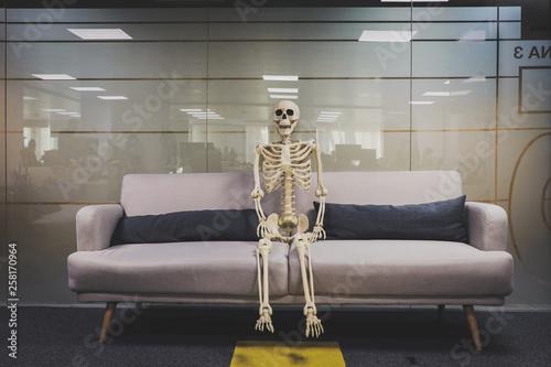 esqueleto en oficina trabajando y muerto de aburrimiento Wallpaper Mural