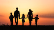 canvas print picture - Silhouettes of happy family holding the hands in the meadow during sunset.