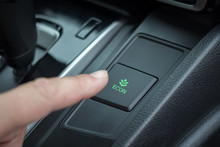 Hand Switching Eco Button In Car Interior, Close Up
