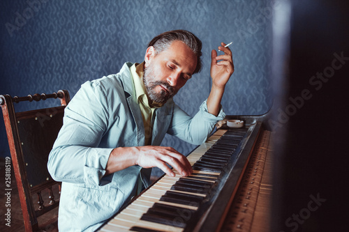 Fotografía  Handsome musician composes music sitting at piano