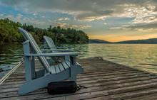 Two Light Blue Adirondack Chairs With A Black Boat Bumper Sits On A Floating Dock On Lake Massawippi At Sunrise Looking East