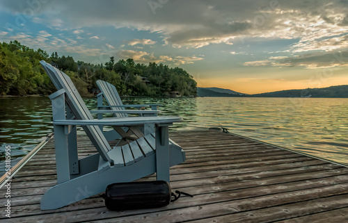 Photo Two light blue adirondack chairs with a black boat bumper sits on a floating doc