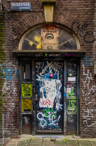 Foto op Plexiglas Graffiti The door to the entrance of the house is painted graffiti