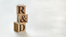 Pile With Three Wooden Cubes - Letters R&D Meaning Research And Development On Them, Space For More Text / Images At Right Side.
