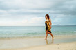 beautiful young girl in pareo walking on the sunset beach on sunlight in Philippines - Summer vacation background