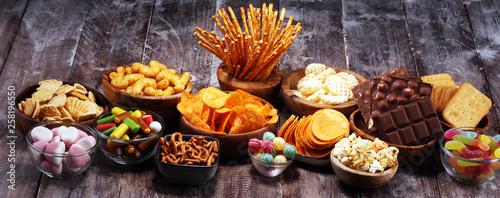 Vászonkép Salty snacks. Pretzels, chips, crackers in wooden bowls on table