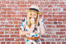 Girl With Fedora Hat Bites Into An Ice Cream Cone In The Summer And Feels Pain Due To Tooth Sensitivity