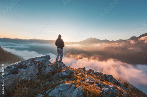 Successful hiker enjoying at top of mountain above clouds - 258200958