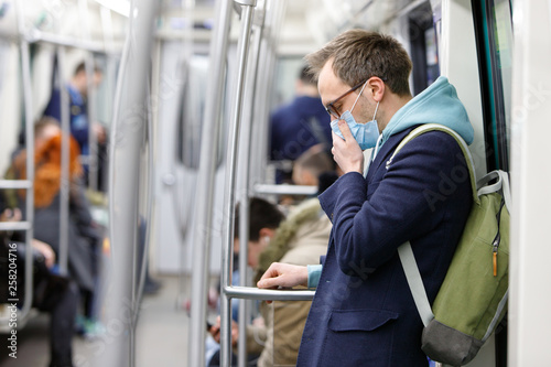 Ill man in glasses feeling sick, coughing, wearing protective mask against transmissible infectious diseases and as protection against the flu in public transport Fototapet