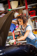 woman mechanic with a wrench adjusts the car's engine
