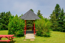 Park With Gazebo And Bench, Painted Red, With Cut Grass And Pine Trees In Nova Scotia Canada