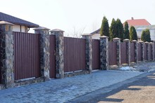 Part Of A Long Brown Fence With A Gate Made Of Wooden Planks And Stones On The Street Along The Gray Asphalt Road