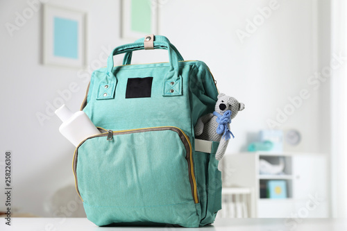 Obraz Maternity backpack with baby accessories on table indoors - fototapety do salonu