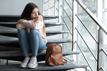 Upset Teenage Girl With Backpack Sitting On Stairs Indoors. Space For Text