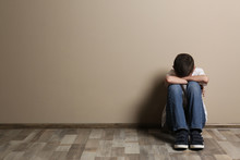Upset Boy Sitting On Floor At Color Wall. Space For Text
