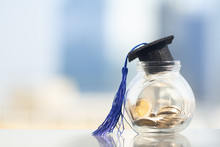 Black Graduation Hat With Blue Tassel On Top Of Glass Jar Or Piggy Bank With Coins On City Background. Education And Scholarship Concept