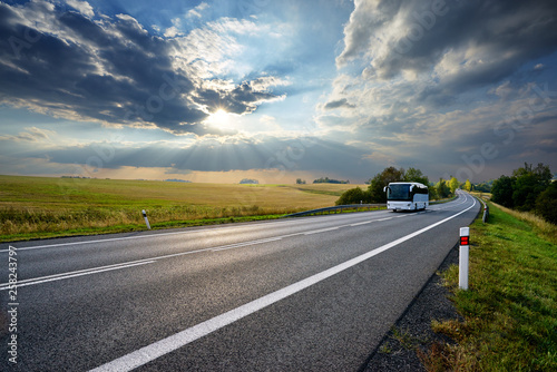 Foto  White bus traveling on the asphalt road in rural landscape at sunset with dramat