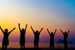 A group of women rise hands up to sky freedom concept with blue sky and beach sunset.