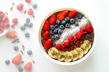 Top View, Acai Berry Superfoods Smoothies White Bowl With Chia Seeds, Strawberry, Goji Berry, Coconut, Blueberry, Raspberry Toppings, And Chocolate Chip On White Background
